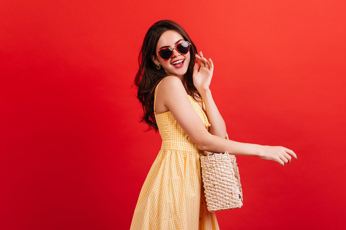 Female model wearing heart shaped glasses wicker bag