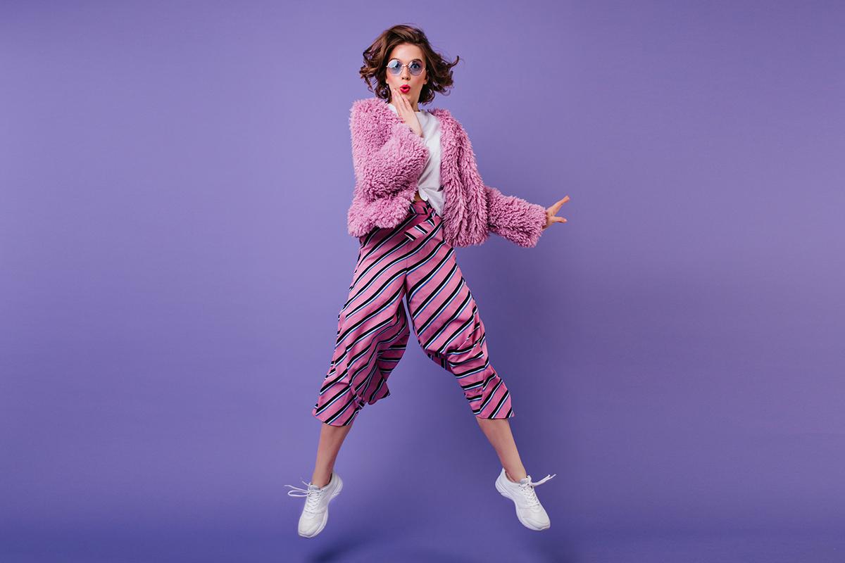 Woman striped pants jumping purple wall indoor portrait wonderful girl sunglasses fooling around