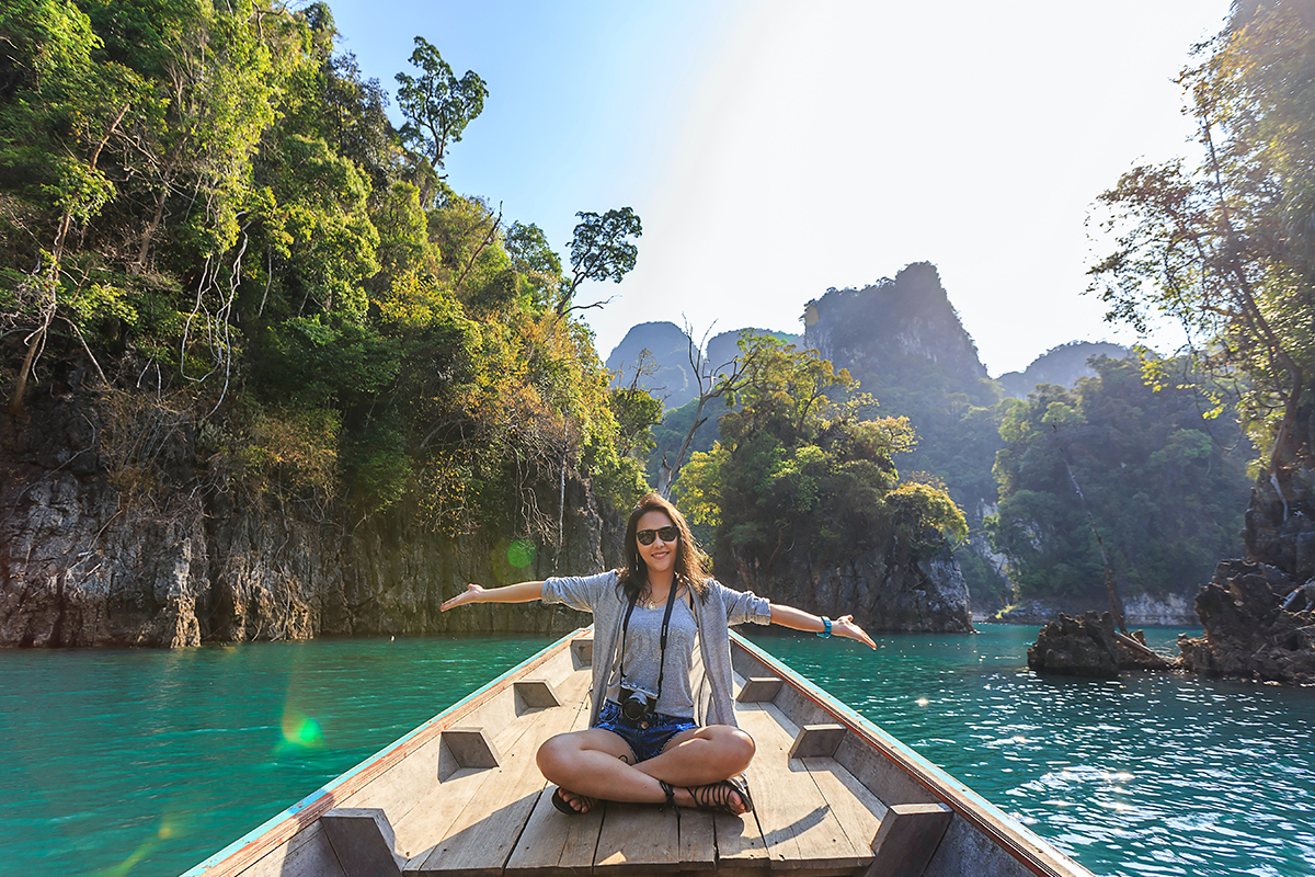 A beautiful girl is sitting in the boat at sea